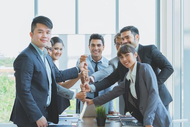 ビジネスチームの握りこぶしのグループは、オフィスで成功するために準備ができて一緒にスタックします。