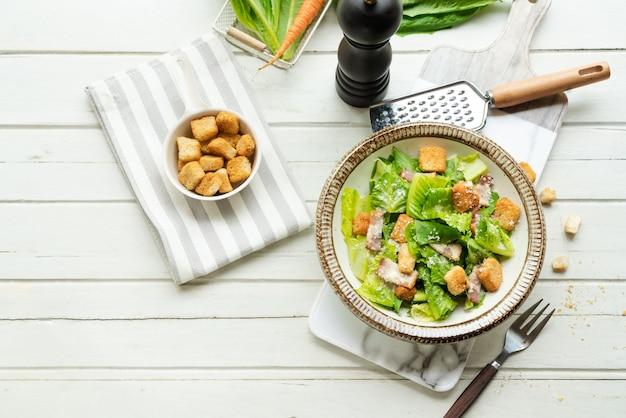 木製の白いテーブルの上皿に新鮮なシーザーサラダ。健康食品、トップビュー