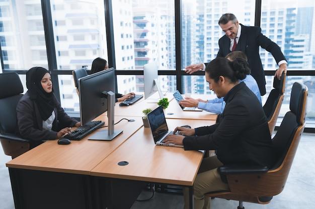 会議後にデスクトップコンピューターとラップトップで働く多様性ビジネス人々のグループ
