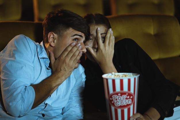 映画館でホラー映画を見ながら手を怖がらせる若いカップルが手を上げる