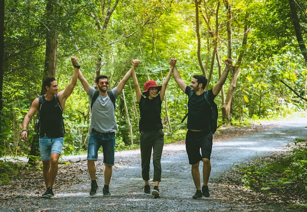 Группа друзей с рюкзаками, веселыми прогулками и поднятыми руками в лесу, приключенческое путешествие