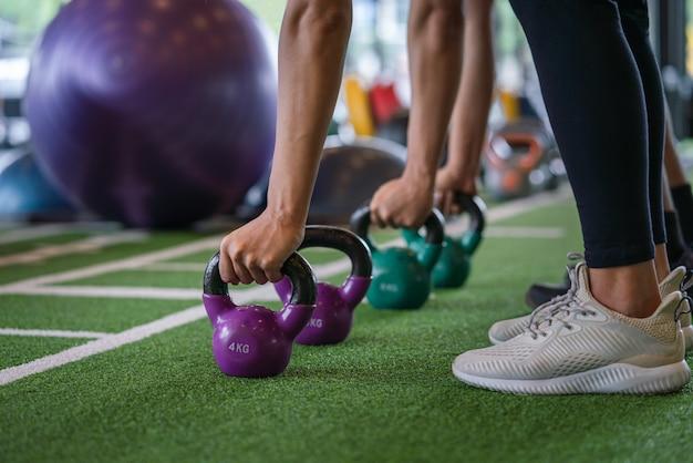運動の若い男性と女性のトレーニングトレーニングとフィットネスジムスポーツクラブでケトルベルの重量と運動のグループ