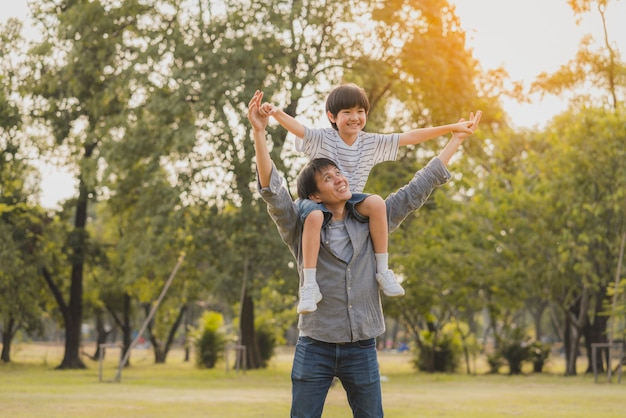 Счастливый и весёлый азиатский папа катает сына на своих плечах, словно летит в парке