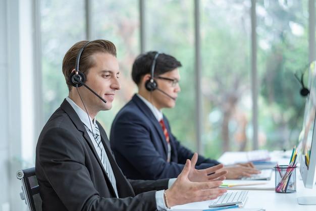 コールセンターのオフィスで顧客と話しているヘッドフォンを着て顧客サービスを働いている男の笑みを浮かべてください。