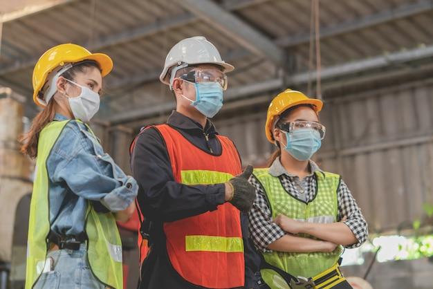 Работники бригады в защитной маске и спасательном жилете на работе