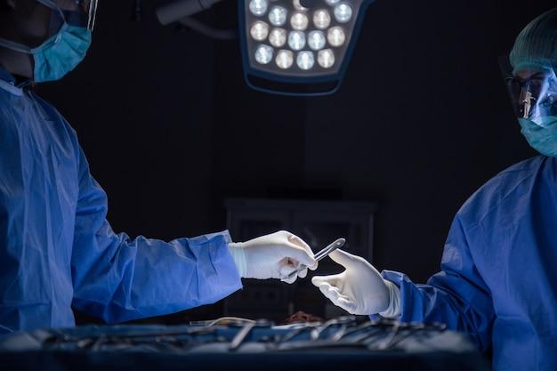 外科的なツールを保持している手袋の手のクローズアップ手術室で手術している外科チーム。