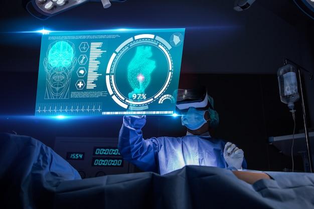 Доктор с виртуальной реальностью в операционной комнате в больнице. хирург, анализируя результаты тестирования сердца пациента и анатомии на технологическом цифровом футуристическом виртуальном интерфейсе