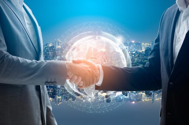 握手のビジネスマンのクローズアップ。グローバルネットワークとフォアグラウンドの世界地図