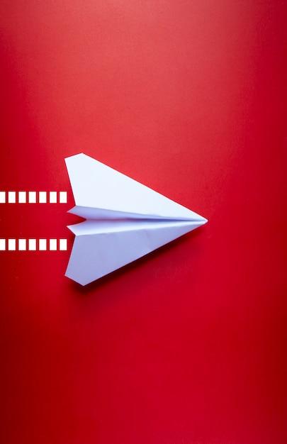 Закройте вверх бумажный самолетик с изолированной предпосылкой