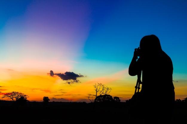 日没の背景を持つシルエット写真家