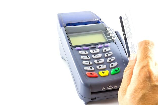 白い背景にあるクレジットカードマシンでクレジットカードを手に