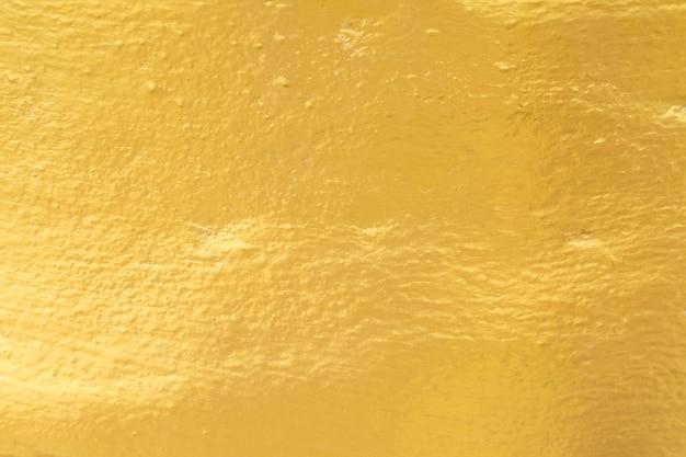 セメントの壁のテクスチャの背景にゴールドペイント