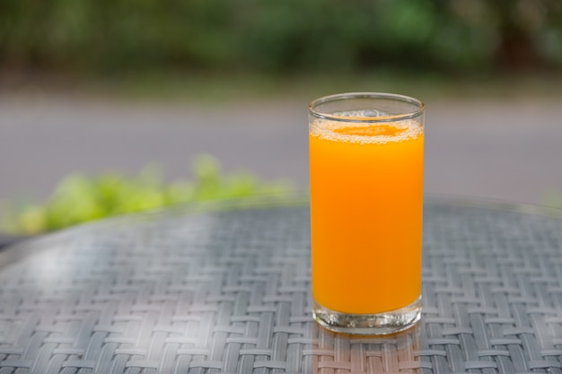緑の背景とテーブルガラスのオレンジジュースグラス