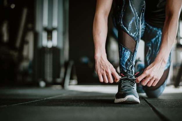 運動前に靴ひもを結ぶ女性
