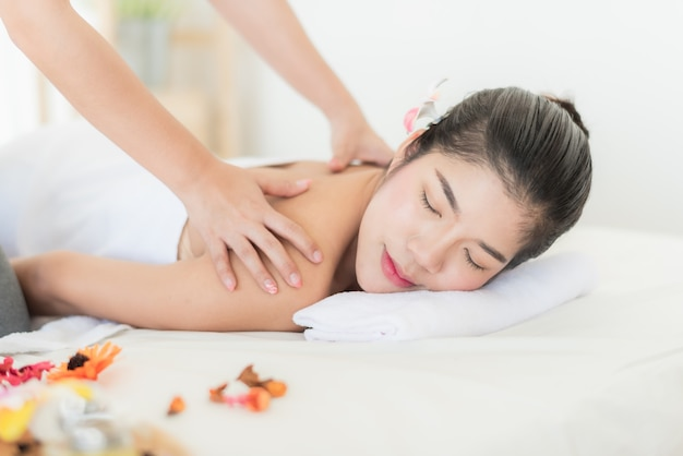 アジア人の女性がベッドに横たわって、マッサージでリラックス