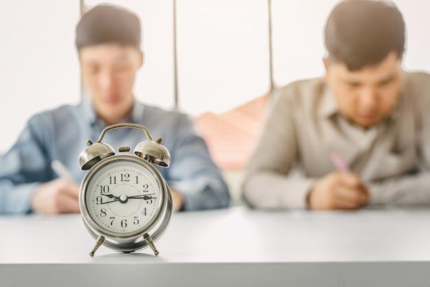 背景でテストをしている男性と目覚まし時計