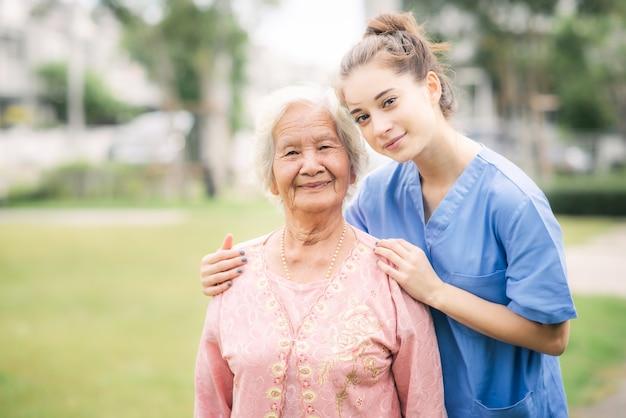 Попечитель с азиатской пожилой женщиной на открытом воздухе