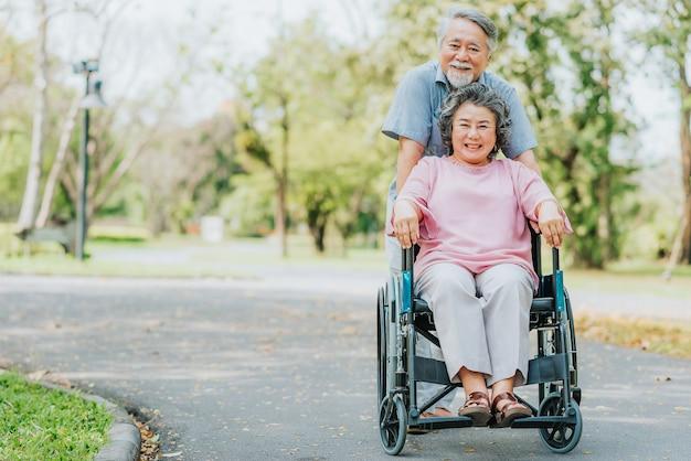 幸せな笑顔アジア人女性は車椅子でリラックスし、彼女の夫と歩いて