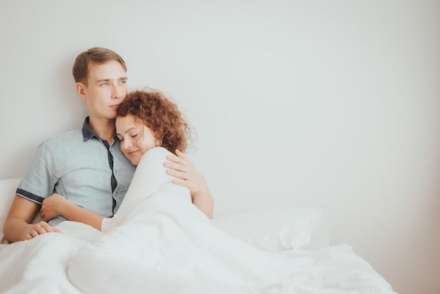 ロマンチックな若いカップルはベッドの上を抱いて