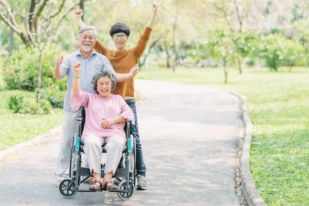 Счастливая семья со старшей женщиной в инвалидной коляске в парке