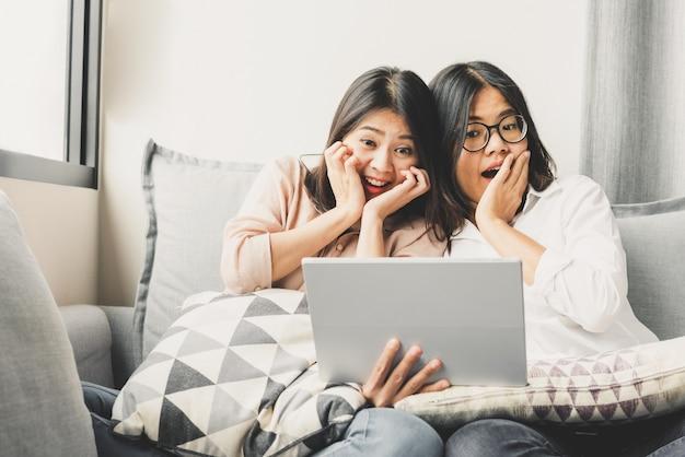 Две азиатские женщины почувствуют удивление и возбуждают, наблюдая за таблеткой