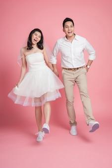 ピンクの上を一緒に歩いてカジュアルなウェディングドレスのアジアカップル