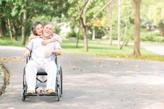 Старшая женщина обнимает своего мужа в инвалидной коляске сзади