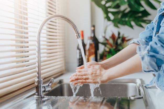 台所で調理する前に流しで手を洗う女