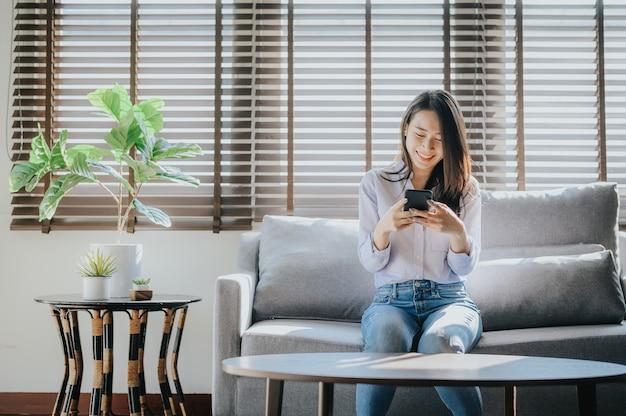 Счастливая женщина текстовых сообщений на смартфоне, сидя на диване