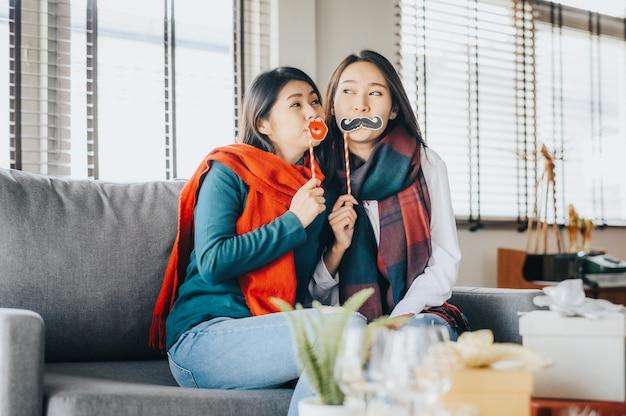 Две азиатские лучшие подруги веселятся во время новогоднего праздника