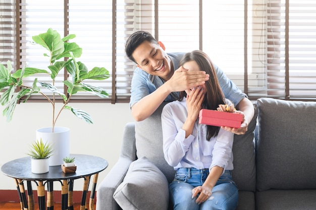 自宅で彼のガールフレンドを驚かせるギフトボックスプレゼントを与えるアジア人