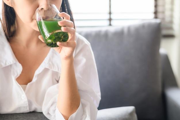 Женщина пьет здоровый зеленый детокс сок