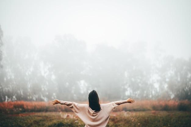 リラックスして朝霧の自由を楽しんでいる女性