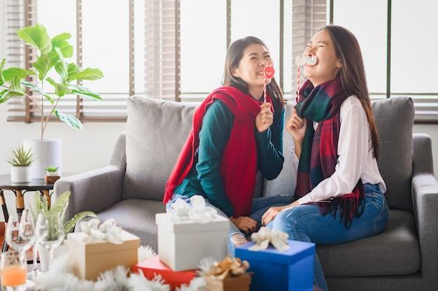 Две азиатские женщины лучшие друзья веселятся вместе в течение нового года