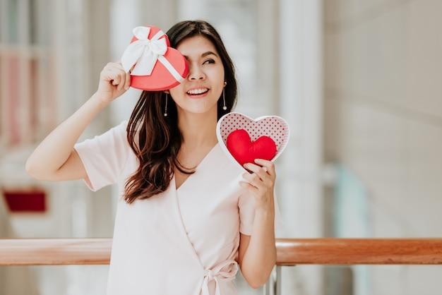 Азиатская женщина, держащая подарочной коробке на день святого валентина, с удовольствием