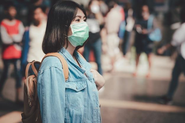 公共エリアでフェイスマスクを身に着けている女性観光旅行