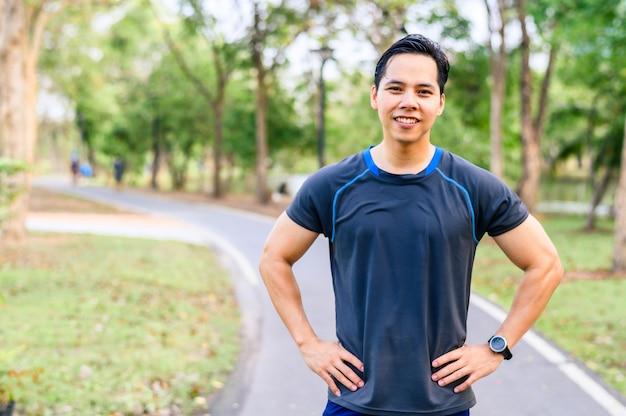 彼は公園で走っていた後、汗をかくアジア人ランナー