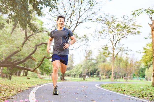 朝は公園で走っている幸せなアジア男