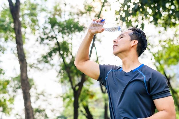 公園でのランニングを終えた後、顔に水を注ぐランナー