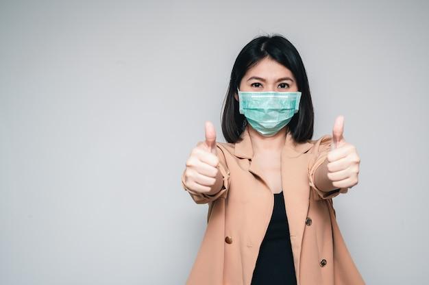 Маска азиатской женщины нося показывая большой палец руки вверх