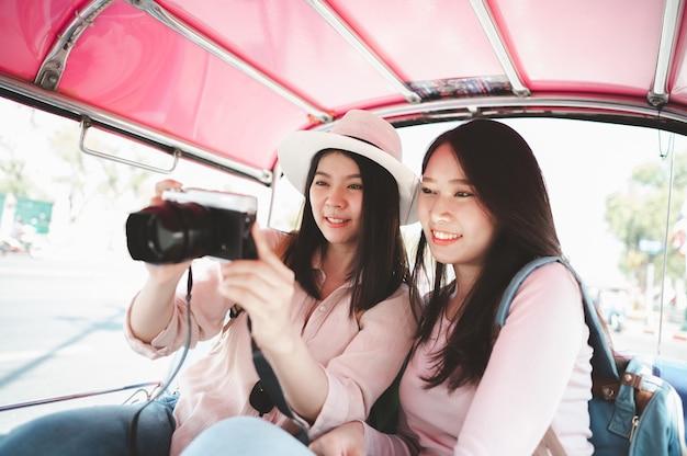 女性旅行者がトゥクトゥクタクシーで旅行中に写真をチェック