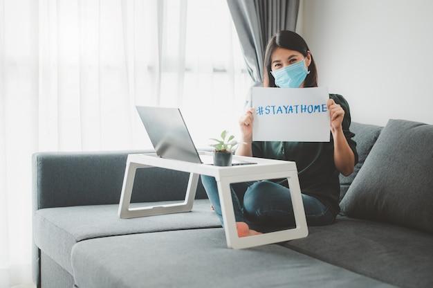 Маска для лица женщины нося работая дома показывая знак пребывания дома
