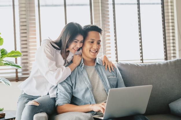 自宅のソファーでノートパソコンを使用して愛の幸せなカップル
