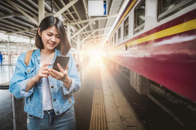 駅のホームでスマートフォンを利用した女性観光客