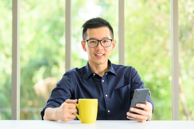 スマートフォンモバイルを使用してアジアの男性の笑顔