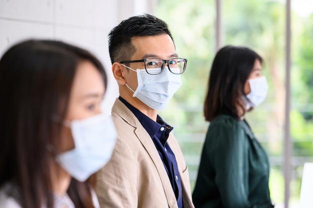 アジアの人々の列は安全のために防護マスクを着用しています