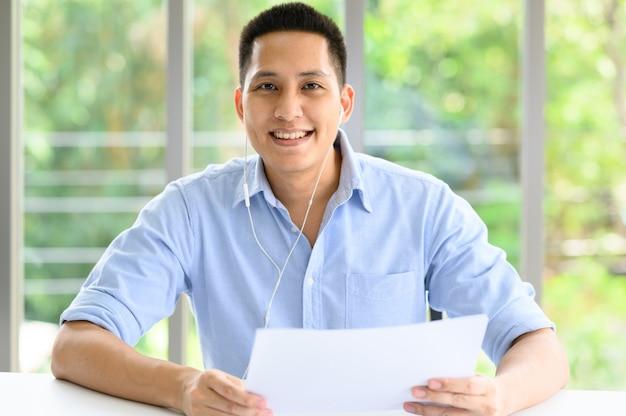 近代的なオフィスに幸せな笑みを浮かべてアジア男