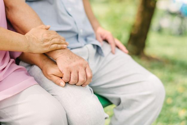 公園で一緒に座っている間手を繋いでいる年配のカップル