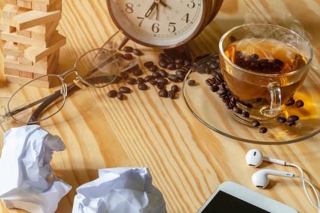 ソーサー、コーヒー豆、ヘッドフォン付き電話。木の背景に隔離されています。ビジネス