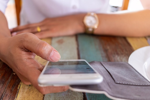 レストランで食べ物の注文を待っている間に電話で電子ゲームをしている女性